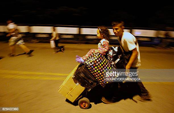 TOPSHOT A man walks hurriedly carrying suitcases on the Simon Bolivar bridge on the Colombian border with Venezuela on December 12 2016 Venezuelan...