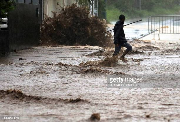 TOPSHOT A man walks in a flooded street in SaintPierre on the French Indian Ocean island of La Reunion on January 18 as the tropical storm Beguitta...