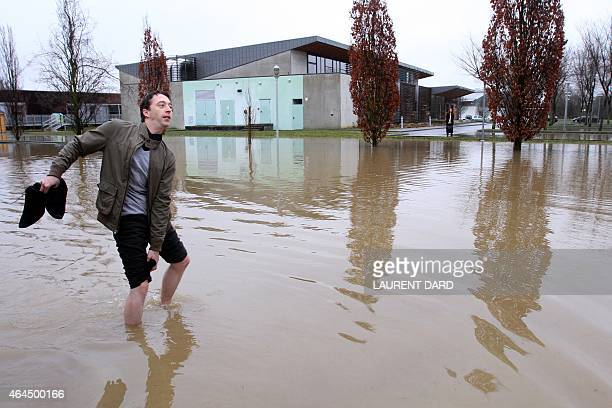 A man walks in a flooded street of the city of Tarbes southern France on February 26 2015 after heavy rains AFP PHOTO / LAURENT DARD