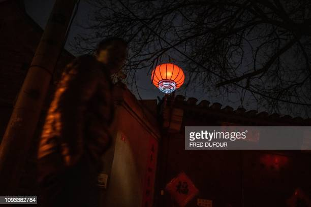 A man walks in a hutong traditional Beijing courtyards ahead of the upcoming Lunar New Year in Beijing on February 3 2019 Millions of Chinese are...