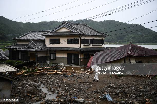 Man walks in a landslide site caused by heavy rain in Tsunagi, Kumamoto prefecture on July 7, 2020. - Emergency services in western Japan were...