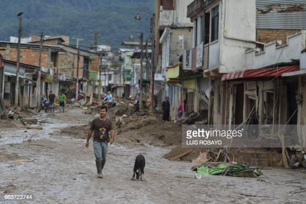 A man walks in a muddy street following mudslides caused by heavy rains in Mocoa Putumayo department southern Colombia on April 2 2017 The death toll...
