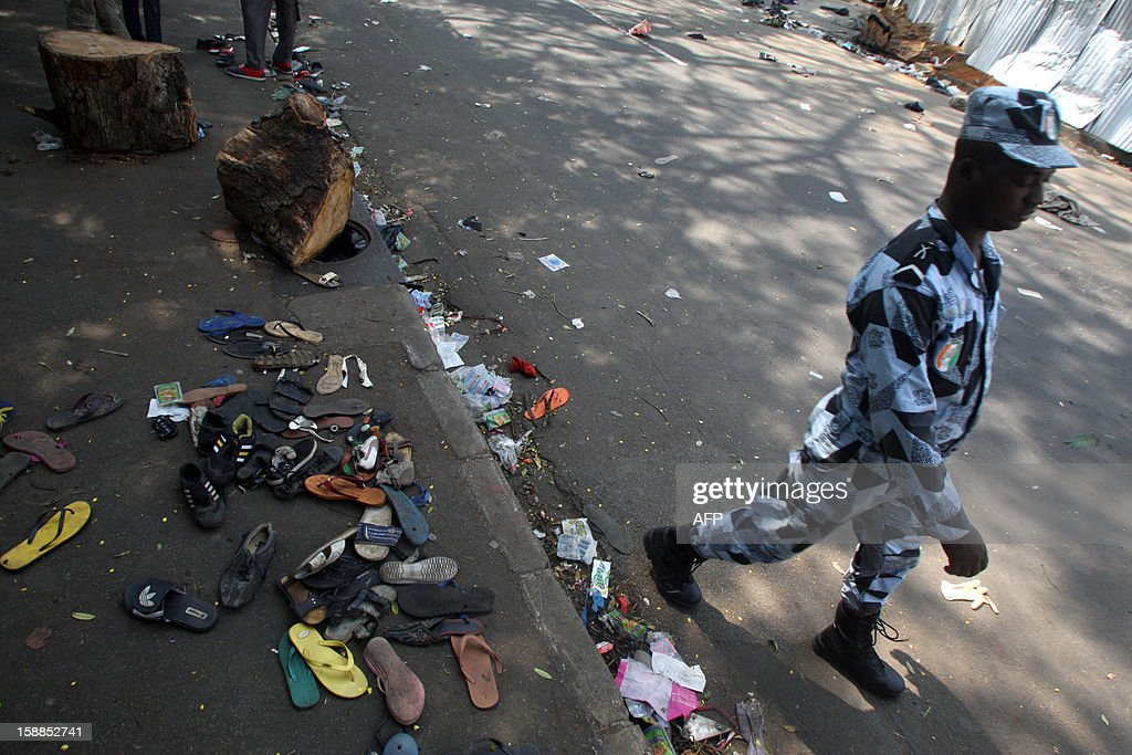 A man walks in a street as shoes are scattered on the pavement at the scene of a stampede in Abidjan, on January 1, 2013. At least 61 people died and dozens more were injured in Abidjan as crowds that had gathered for celebratory New Year's fireworks stampeded overnight, Ivory Coast rescue workers said on January 1, 2013.