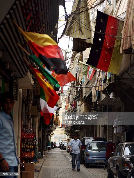 A man walks in a street decorated with a German national flag and other European flags in the Armenian quarter of Bourj Hammoud of the Lebanese...