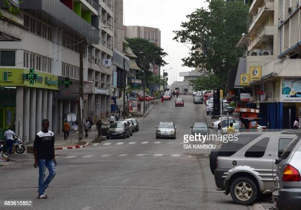 A man walks in a street of Plateau the buisness and administratives district of Abidjan on May 16 2017 Heavy gunfire rang out on May 15 in Ivory...