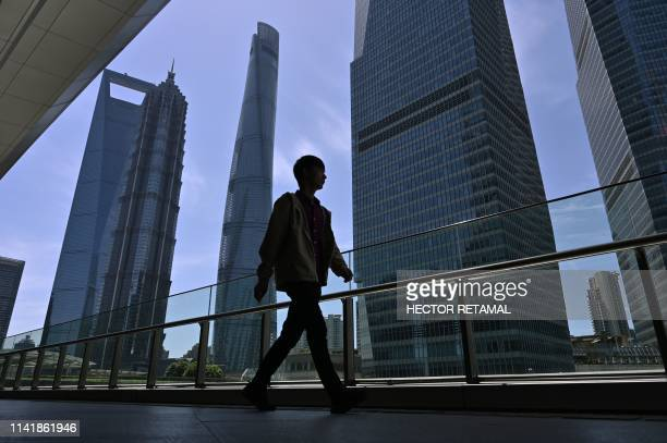 Man walks in a street of the financial district of Lujiazui in Shanghai on May 7, 2019.