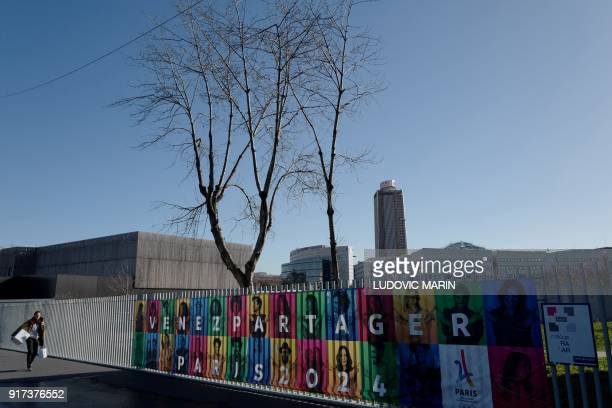 A man walks in a street past a banner promoting the 2024 Olympic Games hosted in France on Febuary 12 2018 in SaintDenis northern suburbs of Paris...
