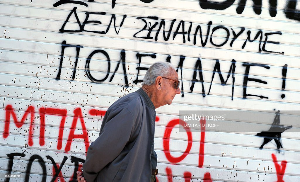 A man walks in downtown Athens on May 2, 2010 next to a slogan reading 'We do not agree - We have war'. Greece plans new budget cuts of 30 billion euros over three years with the aim of slashing the public deficit to less than three percent of output by 2014, Finance Minister George Papaconstantinou said Sunday.