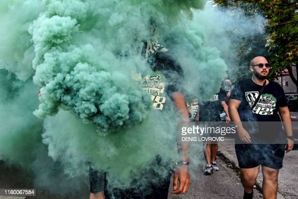 Man walks in flare smoke as he arrives with some 2000 fellow supporters of Hungarian football club Ferencvaros at the Maksimir Stadium in Zagreb on...