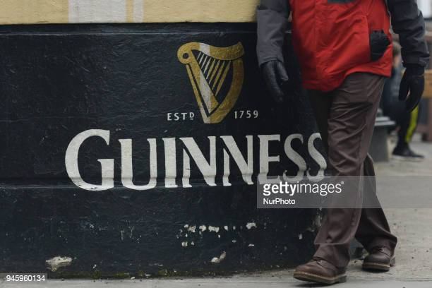 A man walks in front a Guinness add outside a traditional Dublin Pub in the city center On Friday April 13 in Dublin Ireland