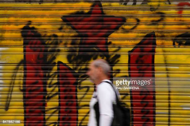 TOPSHOT A man walks in front of a graffiti depecting an Estelada on September 16 2017 in Barcelona More than 700 Catalan mayors who face arrest over...