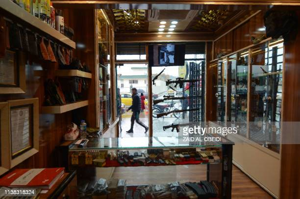 A man walks in front of a gun shop in the northern Iraqi city of Mosul on January 28 2019 Hunting rifles pistols and towers of ammunition magazines...