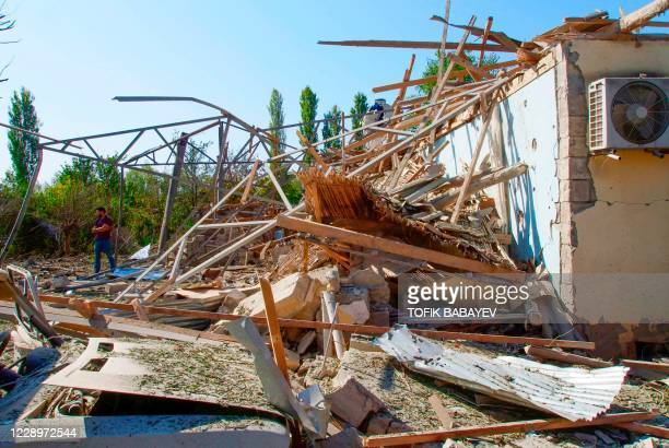 Man walks in front of a house which is said was damaged in shelling during the ongoing conflict between Armenia and Azerbaijan over the disputed...