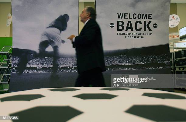 Man walks in front of a huge poster promoting Brazil 2014 FIFA World Cup during the Soccerex Brasilia Forum 2009 opening ceremony on March 17, 2009...