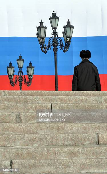 A man walks in front of a huge Russian flag hanging on the Moskva Hotel's facade at the central Manezhnaya Square just outside the Kremlin in Moscow...