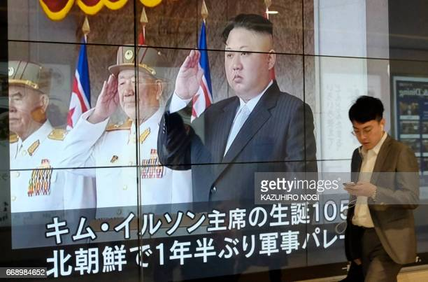 A man walks in front of a news video reporting North Korean leader Kim JongUn at a military parade marking the 105th anniversary of the birth of late...