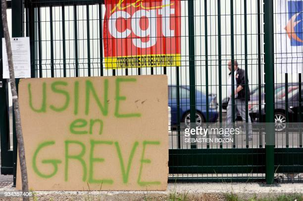 A man walks in front of a plant owned by Visteon a company specialized in automobile components and a supplier of France's PSA Peugeot Citroen in...