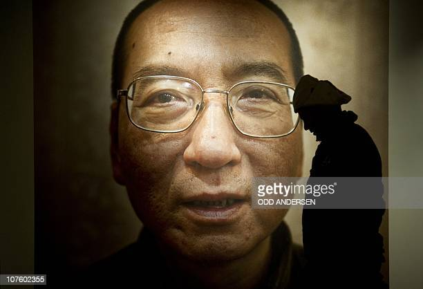 A man walks in front of a poster of Chinese dissident and peace prize laureate Liu Xiaobo at an exhibition at the Nobel Peace Center in Oslo December...