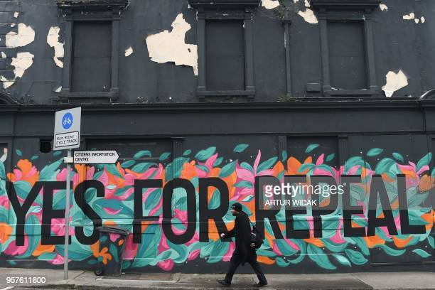 TOPSHOT A man walks in front of a prochoice mural urging a yes vote in the referendum to repeal the eighth amendment of the Irish constitution a...