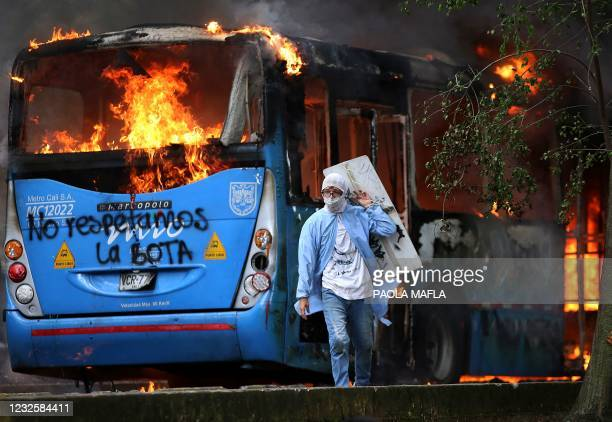 Man walks in front of a public transportation bus in flames during a protest against a tax reform bill launched by Colombian President Ivan Duque, in...