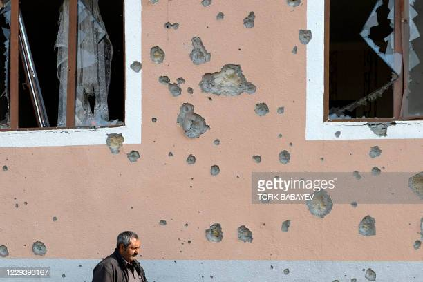 Man walks in front of a residential building damaged in shelling during the ongoing military conflict between Armenia and Azerbaijan over the...
