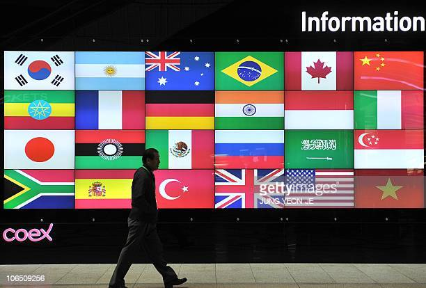 A man walks in front of a screen showing flags of the participating nations for the upcoming G20 Summit at its venue in Seoul on November 4 2010...