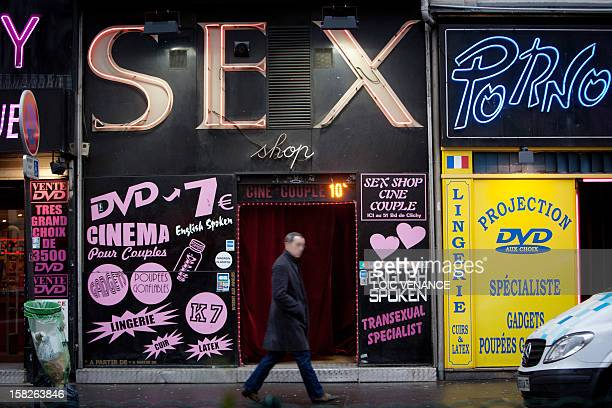 A man walks in front of a sex shop on January 12 2011 in the Paris district of Pigalle AFP PHOTO LOIC VENANCE
