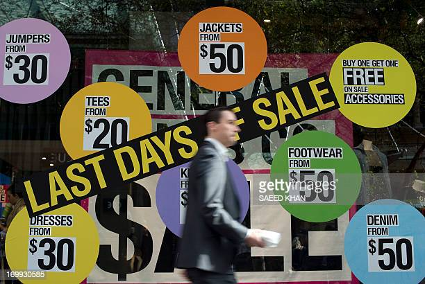 A man walks in front of a shop displaying items on sale in the central business district of Sydney on June 5 2013 Australia's economy grew a...