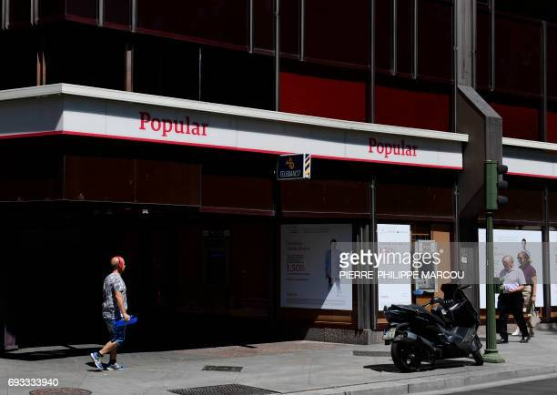 A man walks in front of a Spanish Banco Popular's office in Madrid on June 7 2017 after European authorities announced the sale of Spain's Banco...