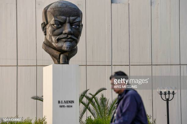 A man walks in front of a stern bust of Lenin at the yard of the Greek Communist party compound in Athens on September 26 2018 The Greek Communist...