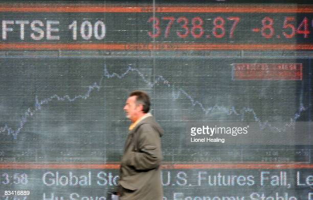 A man walks in front of an electronic sign showing the FTSE 100 share index on October 24 2008 on London England The FTSE fell by more than 300...