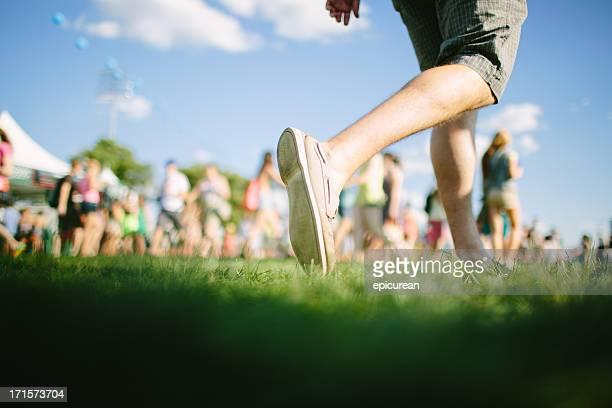 Mann geht in front of Menge an music festival