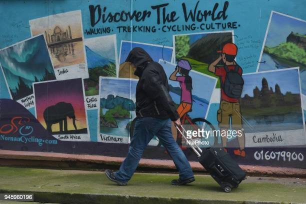 A man walks in front of Discover The World mural in Dublin's city center On Friday April 13 in Dublin Ireland
