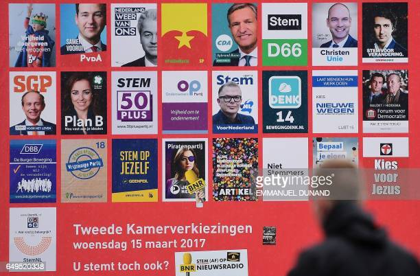 A man walks in front of electoral posters in Leiden on March 8 2017 The Dutch parliamentary elections are set to take place on March 15 2017 / AFP...