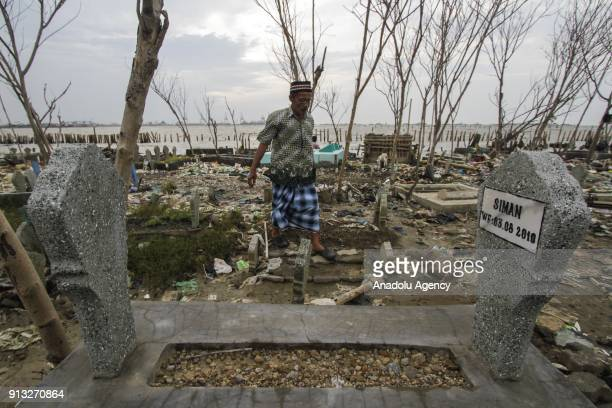 A man walks in front of graves which are inundated by trash following the rising of sea level in Tambak Lorok village of Semarang Central Java...
