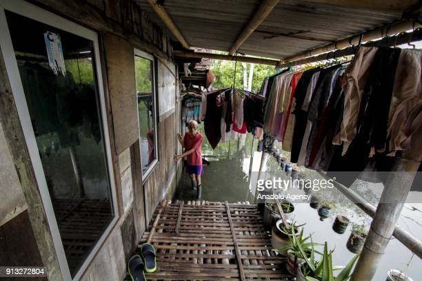 A man walks in front of his waterlogged home in Sriwulan village Sayung subdistrict of Demak regency Central Java Indonesia on February 2 2018 Local...