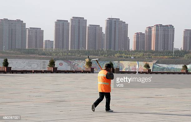 A man walks in front of residential blocks at Kangbashi District on October 16 in Ordos of Inner Mongolia Autonomous Region China