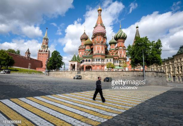 Man walks in front of Saint Basil Cathedral in central Moscow on May 17 during a strict lockdown in Russia to stop the spread of the novel...