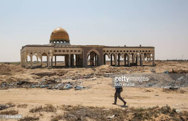 "Man walks in front of the destroyed and deserted terminal of the Gaza Strip's former ""Yasser Arafat International Airport"", in the Palestinian..."