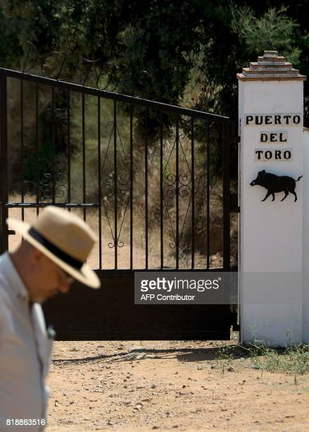 A man walks in front of the entrance gate of 'Puerto del Toro' estate where the former head of Spanish bank Caja Madrid Miguel Blesa was found dead...