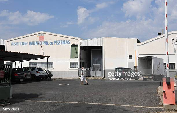 A man walks in front of the municipal slaughterhouse of Pezenas on June 29 2016 after the L214 association released a video denouncing poor animal...