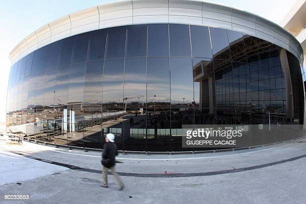 A man walks in front of the new building under construction in the Terminal 1 of Malpensa Airport north of Milan on March 13 2008 The province of...