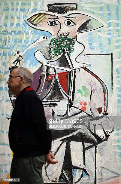 A man walks in front of the painting 'Homme a la Pipe' by Spanish artist Pablo Picasso during a preview of Sotheby's fall sales of impressionist and...