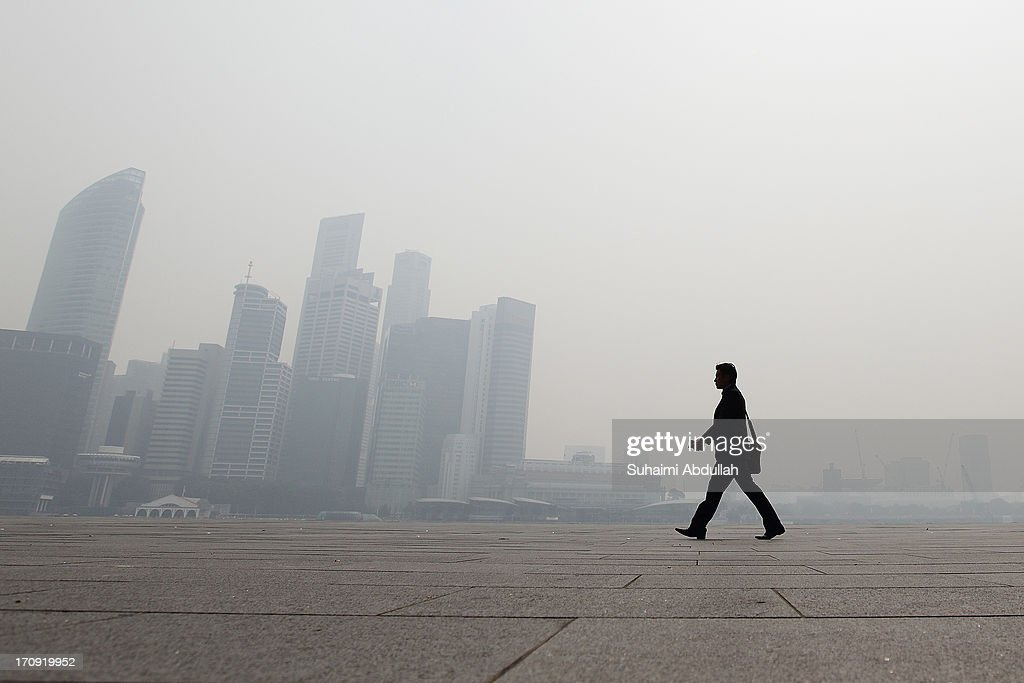 A man walks in front of the Singapore city skyline on June 20, 2013 in Singapore. The Pollutant Standards Index (PSI) rose to the highest level on record reaching 371 at 1pm. The haze is created by deliberate slash-and-burn forest fires started by companies in neighbouring Sumatra.