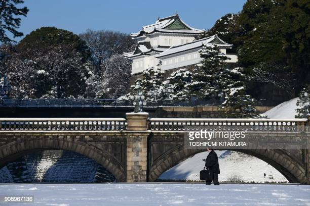 A man walks in front of the snowcovered bridges of the Imperial Palace in Tokyo on January 23 2018 Tokyo woke up to snow across the city a day after...