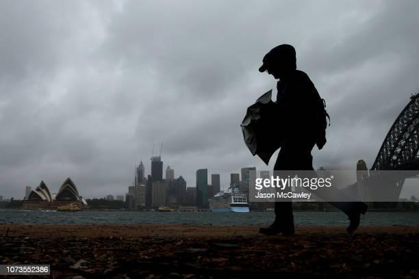 A man walks in high winds on November 28 2018 in Sydney Australia Two months worth of rain is expected to fall within a few hours with the bureau of...