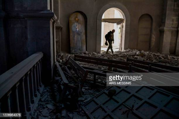Man walks in rubbles on October 8, 2020 inside the Ghazanchetsots Cathedral in the historic city of Shusha, some 15 kilometers from the disputed...
