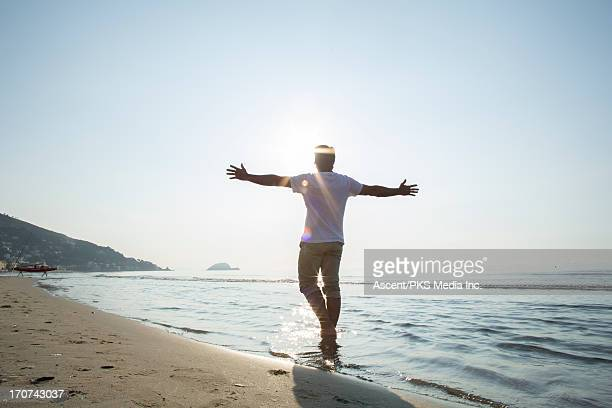 Man walks in shallow sea with oustreched arms