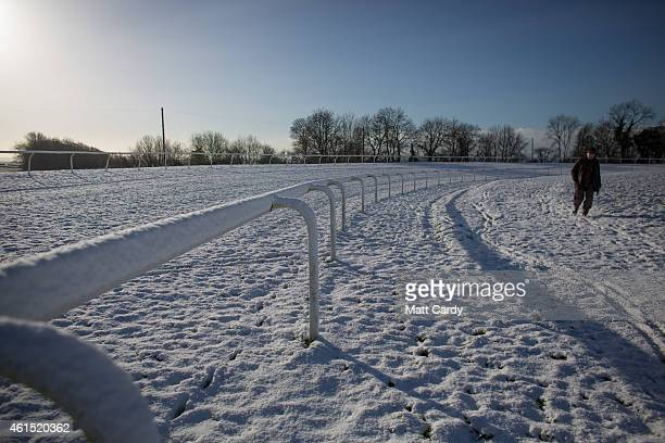 A man walks in snow that has fallen overnight on the Bath Racecourse on January 14 2015 in Bath England Snow has fallen in some parts of the UK and...