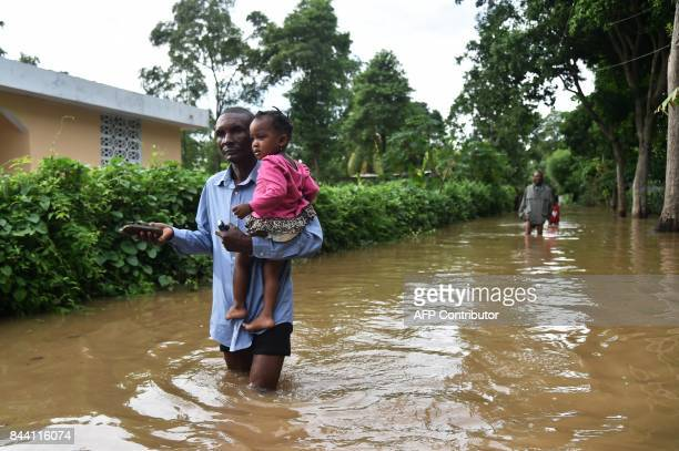 TOPSHOT A man walks in street that was flooded in Malfeti in the city of Fort Liberte in the city of Fort Liverte in the north east of Haiti on...